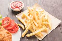 French fries and fried chicken on a wooden table Stock Photo