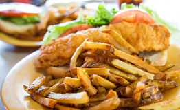 French Fries and Fried Fish Sandwich. A fried fish sandwich on a hoagie roll with fresh french fries, tomato slices and lettuce stock photography