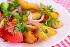 Fried potato slices, boiled broccoli, fresh tomatoes with spices, fresh parsley on a white plate. Easy vegetarian dish. Closeup Royalty Free Stock Photography
