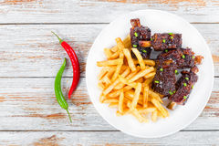 French fries with fried sticky ribs, top view Royalty Free Stock Photo