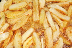French Fries Frying in Oil. Closeup of frying potatoes. It's cooking in boiling sunflower oil and almost ready for consumption royalty free stock images