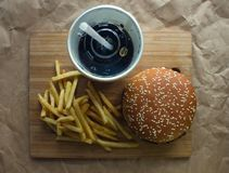 Hamburger french fries and a glass of cola. French fries and a glass of cola on the surface of crumpled paper Royalty Free Stock Image