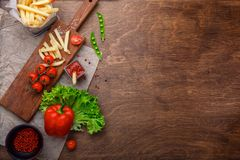 French fries in a grid with ketchup, salad and cherry tomatoes on wooden brown table royalty free stock photos