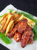 French fries and grilled chicken wings Royalty Free Stock Photos