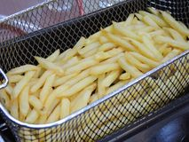 French fries in hot fat in a deep fryer Stock Photos