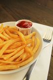 French fries with ketchup. French fries with salt and ketchup in a plate with fork on white napkins Stock Images