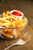 French fries with ketchup. French fries with salt and ketchup in a plate with fork on a wooden table Royalty Free Stock Images