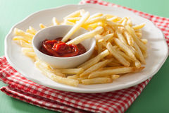French fries with ketchup over green background Royalty Free Stock Photos