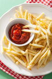 French fries with ketchup over green background Royalty Free Stock Images