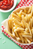 French fries with ketchup over green background Stock Photos