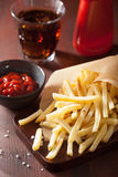 French fries with ketchup over rustic background Royalty Free Stock Photos