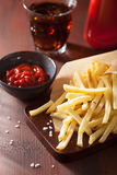French fries with ketchup over rustic background Stock Photos