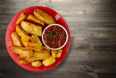 French fries with ketchup on a wooden background. french fries o. N a plate Royalty Free Stock Photo