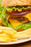 French Fries and Large Cheeseburger Royalty Free Stock Photos