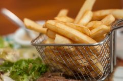 French fries in little metallic basket in a plate at. Closeup of french fries in little metallic basket in a plate at restaurant Stock Photo