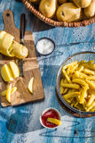 French fries made from potatoes on blue  table Royalty Free Stock Photos