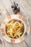 French fries and malt vinegar. On a rustic table Royalty Free Stock Images
