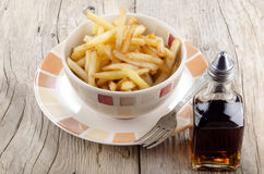 French fries and malt vinegar. On a rustic table Stock Photography