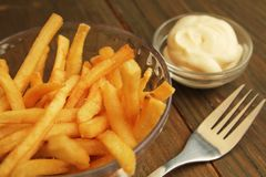 French fries with mayonnaise. French fries with salt and mayonnaise in a clear bowl with fork Stock Photos