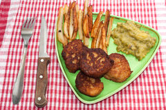French fries with meatballs and peas on a plate and kitchen tabl Stock Photos