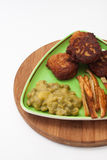 French fries with meatballs and peas on a plate and wooden board Royalty Free Stock Images