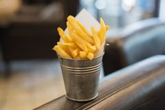 French fries in a metal bucket on a dark surface stock images