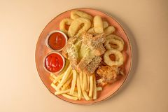French fries, onion rings, chicken wings, rusks, a snack to beer on a large plate with two sauces on a brown background. Top view. Royalty Free Stock Images