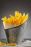 French fries in a pail. French fries in a bucket on the painted wooden table with a beautiful light Royalty Free Stock Photo