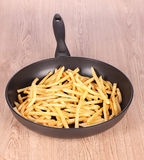 French fries in the pan on a wooden Stock Images