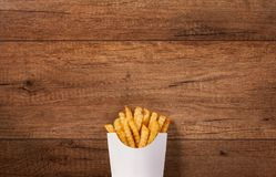French fries in paper bag on the brown wooden table. Large copy space Royalty Free Stock Photo