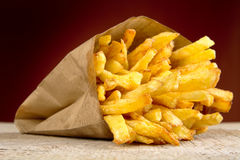 French fries in the paper bag on burned background on wooden table Royalty Free Stock Photo