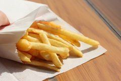 French fries in paper packaging. French fries in a paper box on a wooden board texture Stock Image