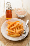 French fries on a paper plate and malt vinegar. French fries on a white paper plate and malt vinegar Royalty Free Stock Photo