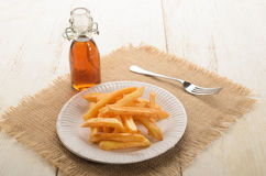French fries on a paper plate and malt vinegar. French fries on a white paper plate and malt vinegar Stock Image