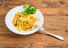 French fries and parsley on white dish and fork Stock Photography