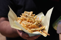 French fries. A patron holds his order of French fried potatoes in a paper container Royalty Free Stock Photography