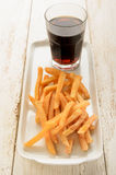 French fries on a plate and a caffeinated brown soft drink Royalty Free Stock Photography