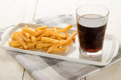 French fries on a plate and a caffeinated brown soft drink Royalty Free Stock Photos