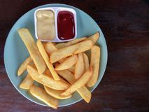 French fries in plate on wood table with mayonnaise and tomato sauce. Top view Stock Photo