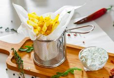 french fries potato in metal basket with sauce stock photo