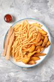 French fries -  potato stick and potato wedges in hot bread. Top view. Copy space. French fries - potato stick and potato wedges in hot bread. Top view. Copy Stock Image