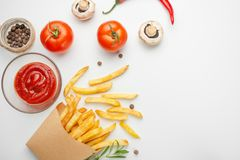French fries with rosemary, fresh tomatoes, mushrooms and sauce in a paper cup on a white background. Delicious and harmful food. royalty free stock photos