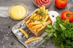 French fries with rosemary sauces and tomatoes on a dark background. Tasty food stock photography