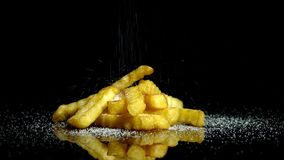 French fries with salt. French fries are strewed by saltisolated on black backgrond , in slowmotion stock video