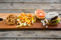 French fries with sauce by onion rings and burger on cutting board Royalty Free Stock Image