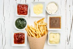 French fries with sauces on white background, top view. French fries wrapped in paper among different sauces in white saucers on the white wooden background with Stock Image