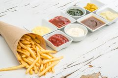 French fries with sauces on white background, top view. French fries wrapped in paper among different sauces in white saucers on the white wooden background with Stock Photography