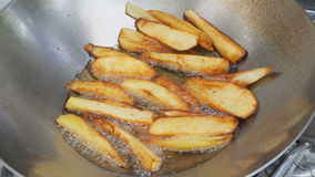 French fries is scorch cooking in hot pan Royalty Free Stock Image