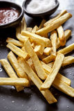 French Fries with Sea Salt on Black Slate. French fries with sea salt and ketchup, on black slate.  Side view Stock Photo