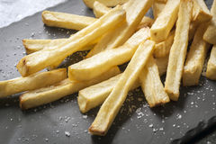 French Fries with Sea Salt on Black Slate. French fries with sea salt, on black slate.  Side view Royalty Free Stock Photography